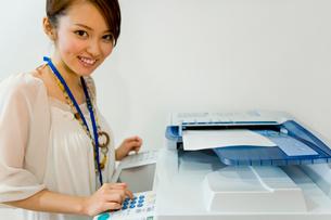 コピー機の前で微笑む女性の写真素材 [FYI03059933]
