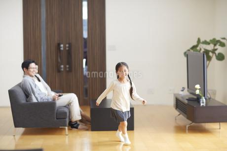 笑顔で歩く女の子と見て微笑む夫婦の写真素材 [FYI03059995]