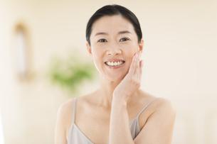 頬に片手を添えて微笑む女性の写真素材 [FYI03059999]