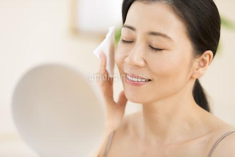 頬にコットンをあてスキンケアをする女性の写真素材 [FYI03060000]