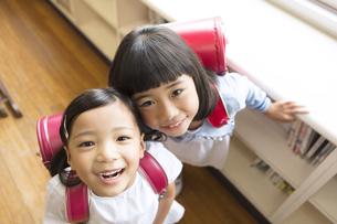 教室でランドセルを背負って笑う女の子2人の写真素材 [FYI03060003]