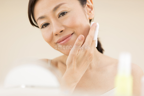 頬にコットンをあてスキンケアをする女性の写真素材 [FYI03060006]