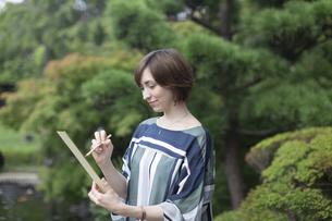 短冊に俳句を書く外国人女性の写真素材 [FYI03060016]