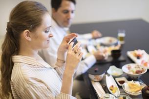 日本料理を撮影する外国人女性の写真素材 [FYI03060017]