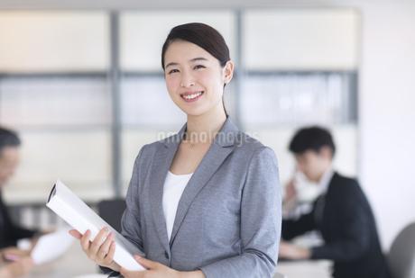 ファイルを持ちカメラ目線のビジネス女性の写真素材 [FYI03060024]