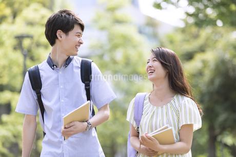 会話をしながら歩く学生の男女の写真素材 [FYI03060026]