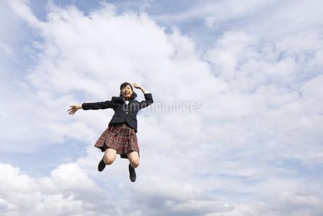 青空をバックにジャンプをする女子高校生の写真素材 [FYI03060035]