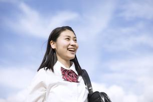 青空をバックに立つ女子高校生の写真素材 [FYI03060045]