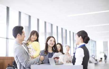 空港カウンターで手続きをする家族の写真素材 [FYI03060054]