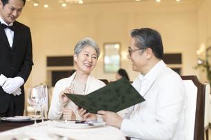 レストランでメニューを見るシニア夫婦の写真素材 [FYI03060060]