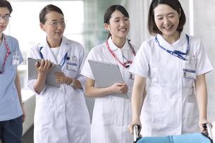 会話をしながら車椅子を運ぶ看護師と医師の写真素材 [FYI03060062]