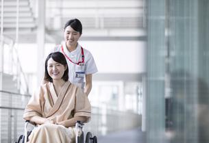 車椅子の患者を押す女性看護師の写真素材 [FYI03060066]