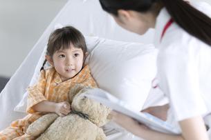 入院患者の女の子に話しかける女性看護師の写真素材 [FYI03060067]