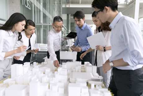 建築模型を使って打ち合せをするビジネス男女の写真素材 [FYI03060072]