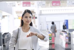 駅の改札付近で時計を確認し周りを見るビジネス女性の写真素材 [FYI03060074]
