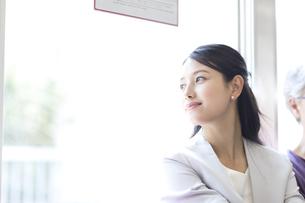 電車で外の景色を見つめるビジネス女性の写真素材 [FYI03060075]