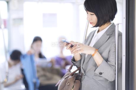 電車でスマホを操作するビジネス女性の写真素材 [FYI03060076]