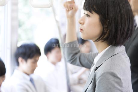 電車でつり革を持ち遠くを見つめるビジネス女性の写真素材 [FYI03060077]