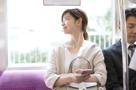 電車で外の景色を見つめるビジネス女性の写真素材 [FYI03060078]