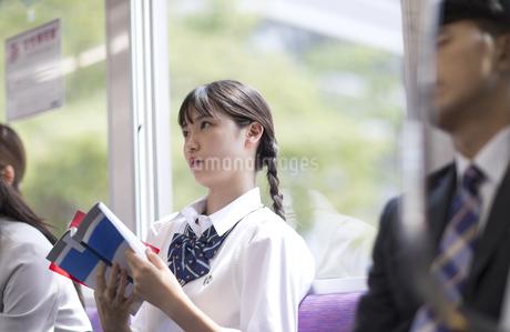 電車で勉強をする女子高校生の写真素材 [FYI03060080]