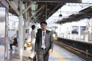駅のホームを歩くビジネス男性の写真素材 [FYI03060082]
