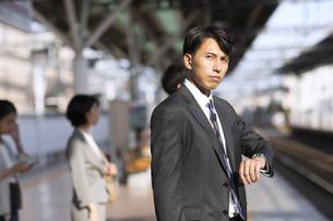 駅のホームで電車を待つビジネス男性の写真素材 [FYI03060084]