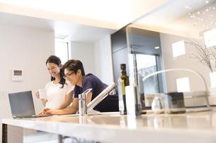 キッチンでパソコンを見る夫婦の写真素材 [FYI03060085]