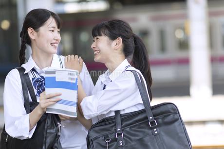 駅のホームで会話をする女子高校生たちの写真素材 [FYI03060086]