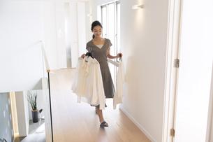 洋服を手に持ち歩く女性の写真素材 [FYI03060089]