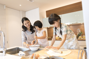 キッチンで料理を作る母親と姉妹の写真素材 [FYI03060096]