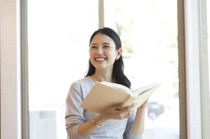 本を持ち笑顔の女性の写真素材 [FYI03060097]
