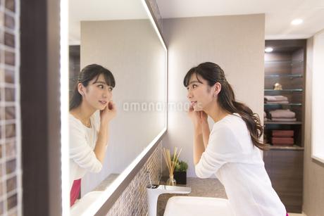 鏡の前でピアスを付ける女性の写真素材 [FYI03060100]