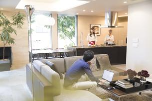 リビングでパソコンを操作する夫と料理をする妻と母親の写真素材 [FYI03060101]