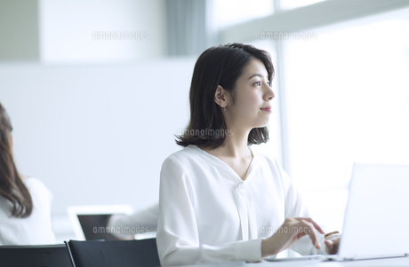 パソコンの前で遠くを見るビジネス女性の写真素材 [FYI03060109]