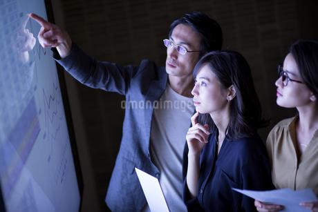 モニターを使って打ち合わせをする男女3人のビジネスマンの写真素材 [FYI03060110]