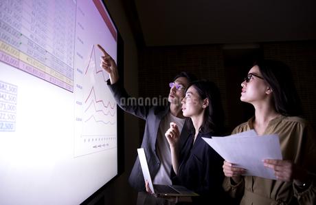 モニターを使って打ち合わせをする男女3人のビジネスマンの写真素材 [FYI03060111]