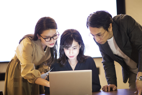 パソコンを見て打ち合わせをする男女3人のビジネスマンの写真素材 [FYI03060112]