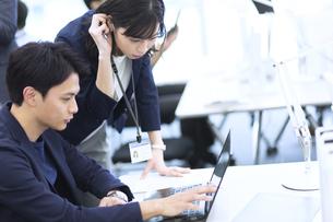 パソコンを見て打ち合わせをする男女のビジネスマンの写真素材 [FYI03060127]