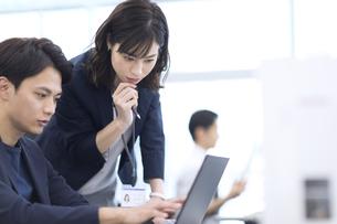 パソコンを見て打ち合わせをする男女のビジネスマンの写真素材 [FYI03060130]