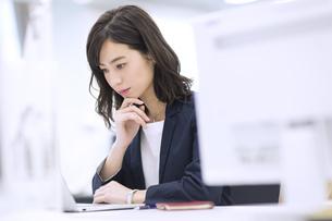 パソコンを見て考えるビジネス女性の写真素材 [FYI03060136]