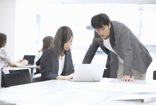 パソコンを見て打ち合わせをする男女のビジネスマンの写真素材 [FYI03060140]