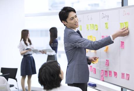 ホワイトボードを使って打ち合わせをするビジネスマンの写真素材 [FYI03060143]