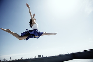 空高く飛ぶ若い女性の写真素材 [FYI03104893]
