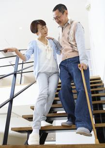 階段を下りるシニア夫婦の写真素材 [FYI03110082]