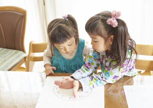 時計の読み方を勉強する姉妹の写真素材 [FYI03110451]