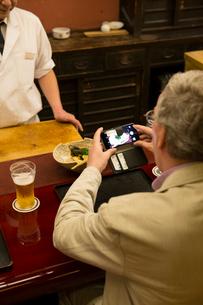 料理の写真を撮る外国人の写真素材 [FYI03113478]