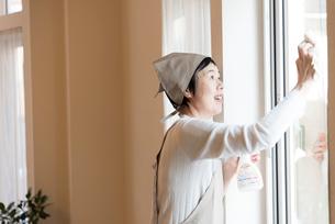 窓掃除をする年配の女性の写真素材 [FYI03114542]