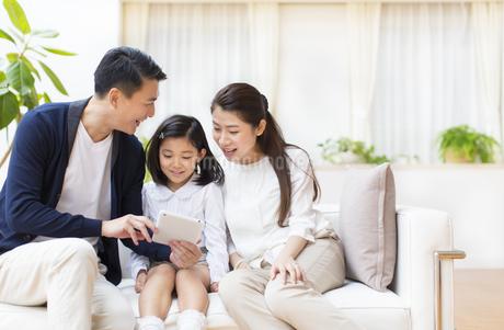 タブレットPCを見ながら笑い合う親子の写真素材 [FYI03114655]