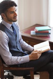 ソファーに座って本を持つビジネス男性の写真素材 [FYI03114659]