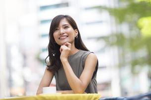 オープンカフェで顎に手をあて上を見上げる女性の写真素材 [FYI03114660]